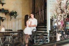 Ideala par som lyckligt kramar nära en spiraltrappuppgång arkivfoton