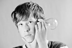 Ideas. A teenager thinking about something and holding a lightbulb Royalty Free Stock Images