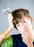 Ideas. A teenage boy thinking of things while holding a lightbulb Stock Photo