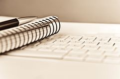 Ideas. A spiral notebook and a pen on a laptop keyboard. Shallow depth of field Stock Photos