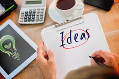 Ideas  against green energy. The word ideas  and man writing on clipboard on working desk against green energy Royalty Free Stock Photography
