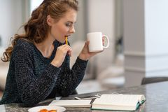 Thoughtful young woman making notes using notepad in kitchen stock photos