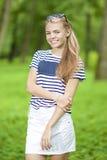 Ideas de la forma de vida del adolescente Adolescente sonriente feliz en la camiseta rayada que presenta al aire libre en bosque Fotos de archivo libres de regalías