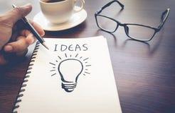 Ideas de los conceptos de la creatividad del negocio dibujo de la bombilla en la libreta imagen de archivo