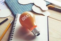 Ideas del negocio con la bombilla en la tabla del escritorio Creatividad, educación imagenes de archivo