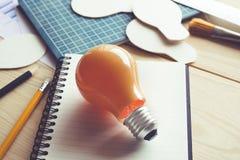 Ideas del negocio con la bombilla en la tabla del escritorio Creatividad, educación imagen de archivo