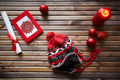 Ideas of gifts. Christmas objects, decorations and red knitted cap on wooden background Stock Photo