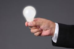 Ideas at Hand. Light bulb shinning at hand with neutral background Royalty Free Stock Photos