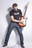 Ideas y conceptos de la música Guitarrista masculino que presenta con la guitarra expresivo contra blanco fotografía de archivo libre de regalías