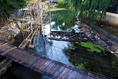 Idee della decorazione del giardino, ponte di attaccatura di legno, ruota idraulica Fotografia Stock