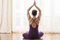 Idee di yoga Metà di yoga di pratica invecchiata della donna caucasica Sedendosi nel vestito porpora del corpo nella posa di rila immagine stock