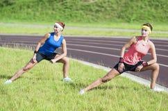 Idee e concetti sani di stile di vita Due giovani amiche caucasiche in abiti sportivi atletici che hanno esercizi di piegamento d Fotografie Stock Libere da Diritti