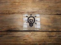 Idee Lampe auf hölzernem Hintergrund stockbilder