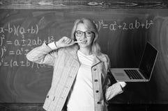 Idee op haar mening De de slijtageoogglazen van de vrouwenleraar houdt laptop surfend Internet Opvoeder slimme slimme dame met mo stock afbeelding