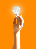 Ideea. Man hand holding a light bulb. Light warmth background. Representing ideea, solution stock image
