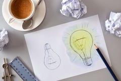 Ideeconcept twee gloeilamp op blad op bureau wordt getrokken dat Stock Afbeeldingen