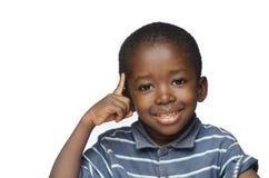 Ideen und Kreativität für Afrika: kleiner schwarzer Junge, der seinen Finger auf sein Hauptdenken zeigt stockfoto