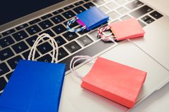 Ideenkaufendes on-line-Konzept: Bunte Papiereinkaufstasche auf Laptop Lizenzfreie Stockfotografie