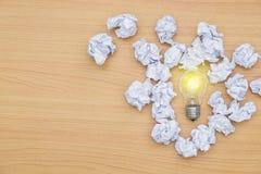 Ideenkonzept-Glühbirne mit Beleuchtung und zerknittertem Papier Stockbilder