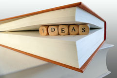 Ideenmitteilung geschrieben in Holzklötze zwischen Buchseiten Lizenzfreie Stockbilder