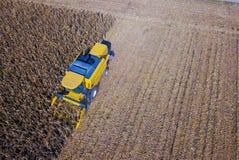 Ideia aérea da colheita mecanizada azul amarela no campo de milho Foto de Stock Royalty Free