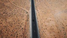 Ideia aérea da condução de carro ao longo da estrada no meio do deserto americano com testes padrões naturais bonitos da paisagem vídeos de arquivo