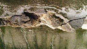 Ideia aérea da inclinação alta do penhasco com pedras brancas e parte inferior do penhasco coberto com a grama verde tiro Contras video estoque