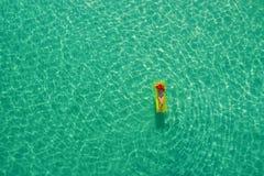 Ideia aérea da natação magro da mulher no colchão da nadada no mar transparente de turquesa em Seychelles Seascape do verão com m imagem de stock royalty free
