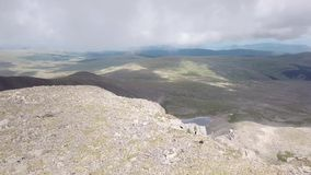 Ideia aérea da parte superior da montanha com muitas pedras e de uma geleira da neve no verão nas montanhas do Altai com grande vídeos de arquivo