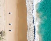 Ideia aérea da praia dos guarda-chuvas, das ondas, do oceano dos azuis e de vibrações de relaxamento fotografia de stock