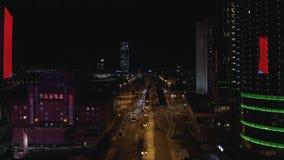 Ideia aérea da vida urbana grande na noite, nas luzes de néon, nos arranha-céus de vidro, nos carros e na grande ponte cruzando o fotografia de stock