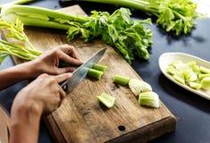 Ideia aérea das mãos com aipo do corte da faca na boa de madeira do corte Fotografia de Stock