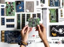 A ideia aérea das mãos com eletrônica do computador parte no fundo branco fotografia de stock royalty free