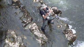 Ideia aérea de movimento lento da pesca do pescador em um rio com uma vara de pesca filme
