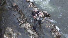 Ideia aérea de movimento lento da pesca do pescador em um rio com uma vara de pesca video estoque