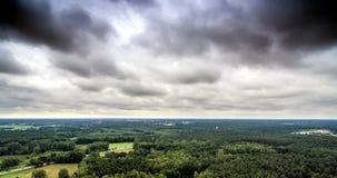 Ideia aérea de uma área arborizada densa em Alemanha, que é cruzada por uma estrada na borda de uma cidade, com céu dramático fotos de stock royalty free