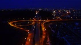 Ideia aérea de uma grande junção de estrada iluminada na noite completamente dos carros e dos caminhões filme