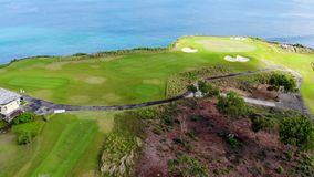 Ideia aérea do campo do golfe em seguida o clif e o oceano vídeos de arquivo