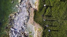 Ideia aérea do litoral ao longo do mar com um penhasco com grandes pedras e um grupo de pessoas de passeio na grama verde filme