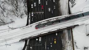 Ideia aérea do tempo de inverno da junção de estrada com carros, ônibus, e o outro tráfego com a ponte de estrada de ferro acima  filme