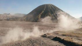 Ideia aérea do tiro cinemático do cavaleiro do motocross que conduz em um deserto empoeirado vulcânico perto da montagem bonita B video estoque