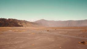 Ideia aérea do tiro cinemático do cavaleiro do velomotor que conduz em um deserto empoeirado vulcânico perto da montagem bonita B video estoque