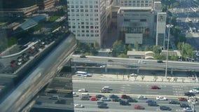 A ideia aérea do tráfego da passagem superior na cidade, reflete na janela de vidro vídeos de arquivo