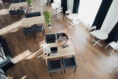 Ideia aérea do trabalho fêmea novo em seu portátil em um café A vista superior disparou do assento fêmea em uma tabela com um cop Foto de Stock Royalty Free