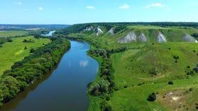 Ideia aérea do voo sobre montes rochosos gramíneos verdes do giz, montanhas e um rio video estoque