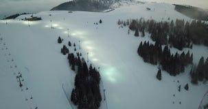 Ideia aérea do zangão da inclinação iluminada do esqui para o esqui da noite Estância de esqui de Monte Pora video estoque