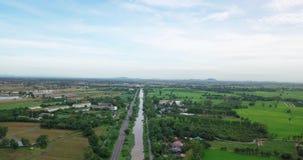 Ideia aérea dos campos com vários tipos de agricultura e de canal da irrigação em Tailândia rural filme