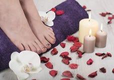 Ideia aérea dos pés desencapados da mulher com os pregos coloridos manicured bonitos que descansam em uma toalha roxa Imagem de Stock