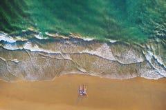 Ideia aérea dos pares asiáticos que encontram-se na praia com as ondas que rolam na costa para o curso, fundo exterior das férias foto de stock