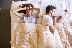 Ideia aérea dos pares com os problemas do relacionamento que encontram-se na cama fotografia de stock